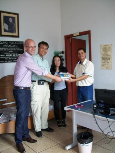O internacionalista Rodrigo Campos (direita), o Professor Akihiro Asakawa e a Professora Naoko Shinkai recebem livros   das mãos do Arquivista Carlos Lima. Foto: Profa. Aparecida Mituiassu, Ago. 2013, Acervo APMOMG